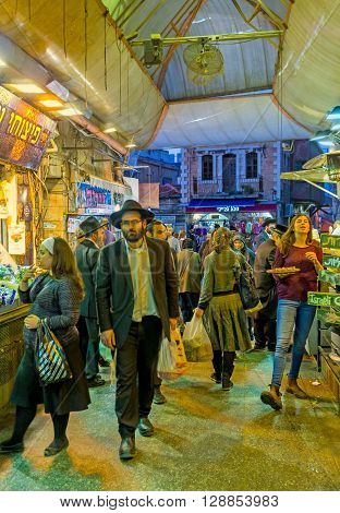JERUSALEM ISRAEL - FEBRUARY 18 2016: The crowded row of Mahane Yehuda market the evening is the hot time for the merchants on February 18 in Jerusalem.