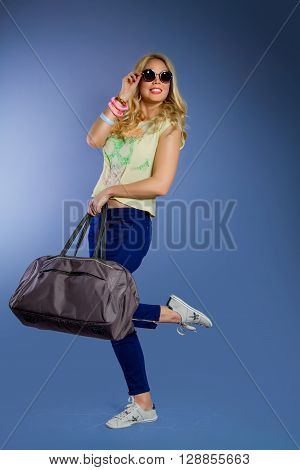 A traveling smiling girl with long blond hair  in sun-glasses is holding a travel bag