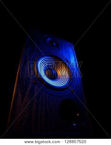 audio speaker illuminated in blue and orange on a black background isolated