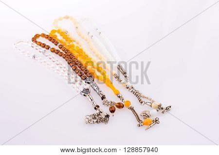 Colorful Tespihs that is prying beads on a white background