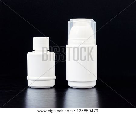 White roll on deodorant and a refill bottle on dark background.