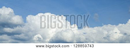 Clouds flying in summer sky panorama. White fluffy clouds carpet