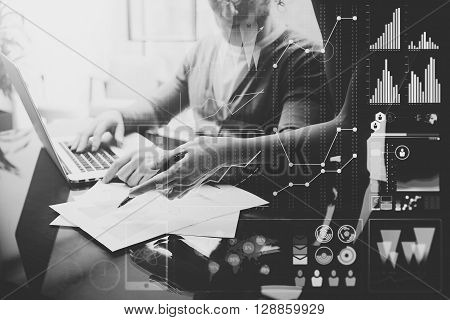 Business concept photo.Meeting of investment managers.Woman showing repots.Man using modern laptop. Graphic icon, worldwide stock exchanges interfaces. Horizontal. Film effect. Black and White