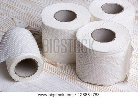 Rolls of toilet paper on wooden board