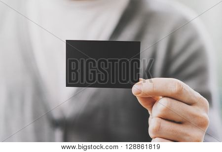 Man wearing casual shirt and showing empty black business card. Blurred background. Ready for private information. Horizontal mockup, fim effects.