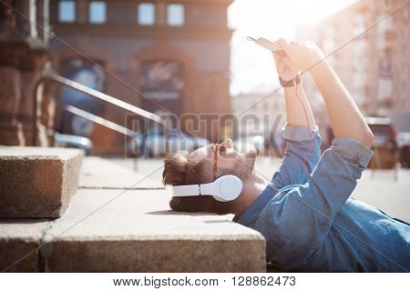 Lighten up. Cheerful delighted handsome smiling guy lying on the footsteps and making photos while listening to music