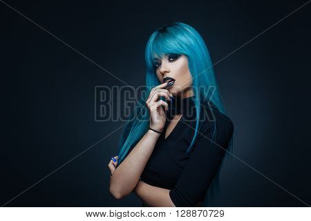 Portrait of a young woman with a cyan color hair