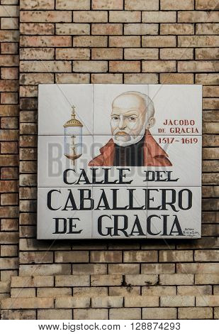 MADRID, SPAIN - MARCH 13, 2016: Closeup of the street sign in Madrid. They are hand-painted ceramic tiles typically composed within 9 or 12 tiles. They depict the name of the alley or street as well as illustrations that indicate special meanings. ** Not