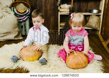 Boy and girl sitting in a barn with a pumpkin on fur