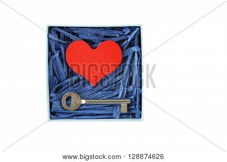 Red painted wooden heart and metal key enclosed with blue paper raffia strips in paper box isolated on white background