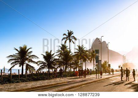 Rio de Janeiro, Brazil - March 27, 2016: People walk along a car-free Avenida Vieira Souto at sunset on Ipanema Beach.