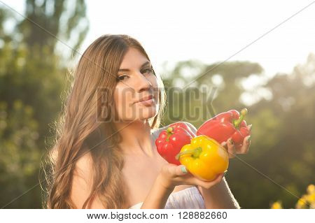 Young woman 20-24 year old holding raw peppers outdoors. Looking at camera. Fall season. Harvesting.