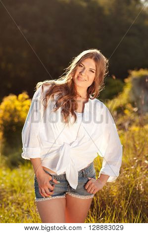 Smiling young woman 25 year old wearing white shirt and denim shorts outdoors. Looking at camera. 20s.