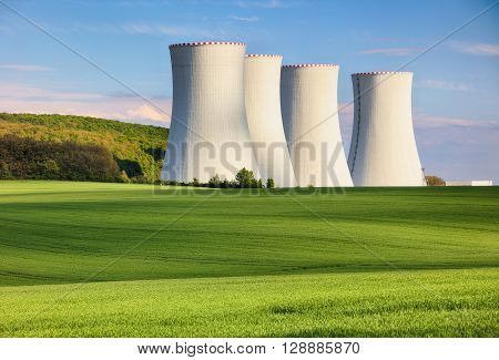 Nuclear power plant with green field at day.