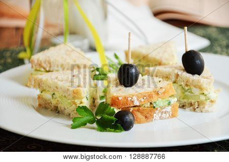 Mini sandwiches cut in triangles and filled with with cucumber, eggs and olives