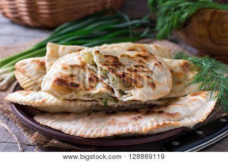 Flat bread with herbs, kutaby, traditional Azerbaijani dish on a plate