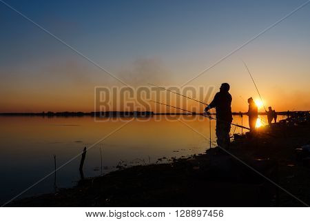 Fisherman catches fish by spinning on the lake at sunset.