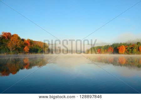 Lake fog with Autumn foliage and mountains with reflection in New England Stowe