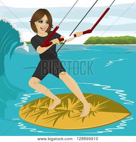 Female kiteboarder enjoys surfing waves with yellow kiteboard