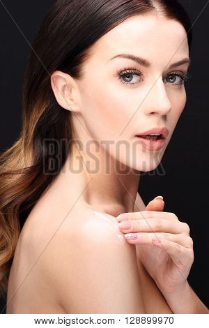 Beautiful and smooth skin, natural beauty of a woman. Beautiful young woman rubbed cream