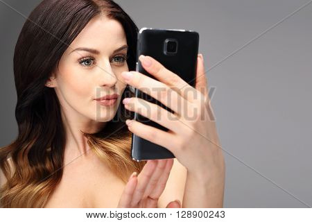 A beautiful young woman browsing the Internet on a mobile phone