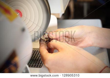Jeweler polishes jewelry for jewelry polisher .