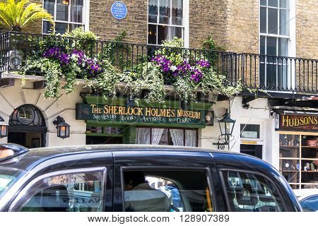 LONDON UK - JUNE 6 2015:Black London taxi on the background of facade of the Sherlock Holmes house and museum in 221b Baker Street. Here is where Arthur Conan Doyle located the studio of the famous detective.