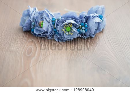 Handmade Wraith Of Blue Flowers Lying On Wooden Background