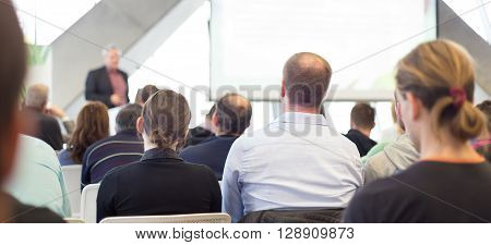 Man giving presentation in lecture hall. Male speeker having talk at public event. Participants listening to lecture. Rear view, focus on people in audience.