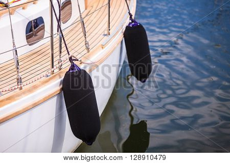 Yachting. Sailboat in the sea different parts of yacht. Side of hull with black fenders