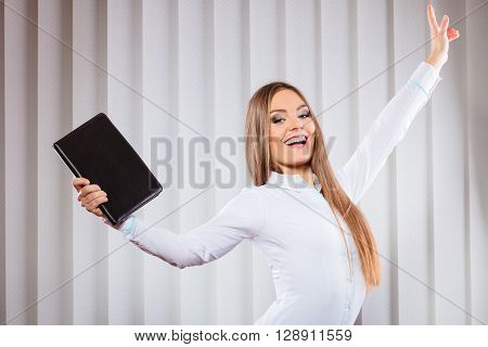 Career business success in work. Young woman in formal wear hold case with files documents paperwork hold hand in air show victory gesture.