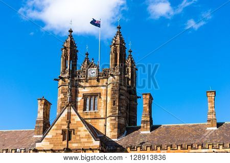 Sydney Uni building facade with Australian flag. University of Sydney against deep blue sky with white clouds daytime photo