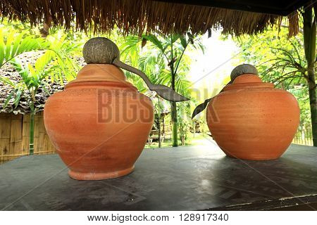 earthen jar in the gardenearthen water jargarden propsThailand traditional water jars used for drinking water.