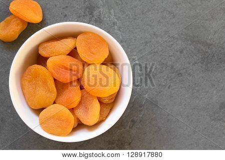Dried apricots a healthy snack containing vitamins beta-carotene fiber antioxidants photographed overhead on slate with natural light (Selective Focus Focus on the apricots on the top)