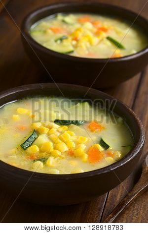 Vegetarian corn and courgette chowder served in rustic bowls wooden spoons on the side photographed on dark wood with natural light (Selective Focus Focus one third into the image)