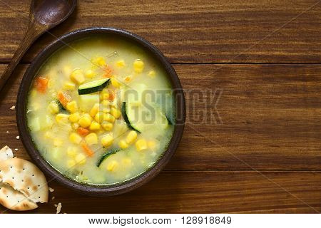 Vegetarian corn and courgette chowder served in rustic bowl saltine cracker and wooden spoon on the side photographed overhead on dark wood with natural light (Selective Focus Focus on the top of the soup)