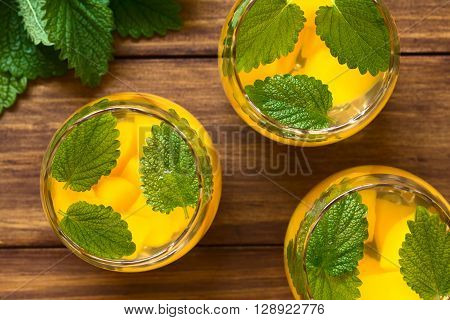 Refreshing peach lemon balm and white wine punch or wine cooler in glasses photographed overhead on dark wood with natural light