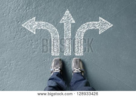 Taking decisions for the future man standing with three direction arrow choices, left, right or move forward