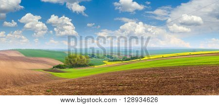 Big panoramic view of beautiful spring hills landscape with colorful fields, sunny day sky