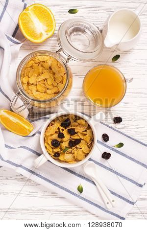 Breakfast concept with corn flakes, milk, dry cranberry and orange juice. Top view