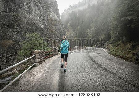 Running on the road around mountains under snowly rain.