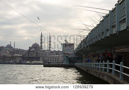 ISTANBUL, TURKEY - JANUARY 02, 2015: Mosque Yeni Cami and Galata bridge cloudy december morning. The landmark of Istanbul