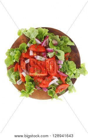 fresh raw vegetable salad with tomatoes and green lettuce on wooden plate isolated over white background
