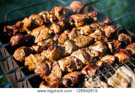 Shashlik (shaslik) - traditional russian barbecue. Pork Shish kebab on Fire. Appetizing fresh meat shish kebab prepared on a grill wood coal outdor