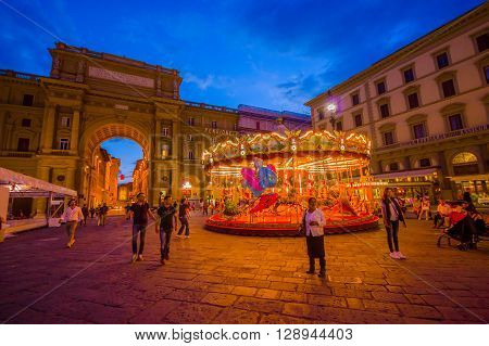 FLORENCE, ITALY - JUNE 12, 2015: Carousel at night iluminated in the middle of the square in Florence. Different forms waitting for childrens, people walking around.