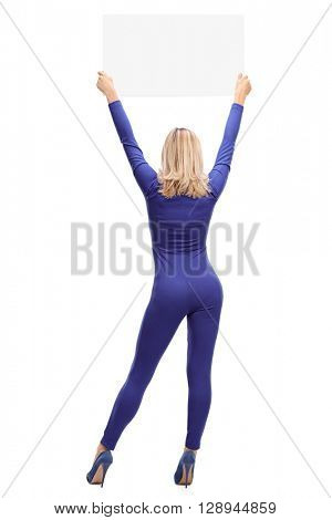 Full length rear view shot of a car racing woman holding a blank sign above her head isolated on white background