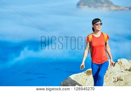 sporty   female traveler with backpack  standing on the cliff against sea and blue sky with white clouds at early morning, Crete, Greece. woman holding the phone smiling and looking at left side