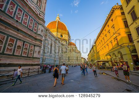 FLORENCE, ITALY - JUNE 12, 2015: Large street on the side of Florence Cathedral, people walking around minutes before sunset, sunlight