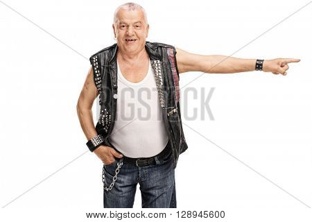Studio shot of a senior punk rocker pointing to the right isolated on white background