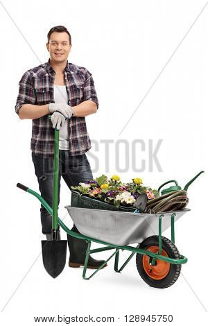 Full length portrait of a young man posing with gardening equipment isolated on white background